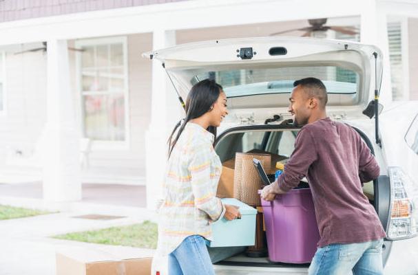 Un couple qui range des affaires dans le coffre d'une voiture