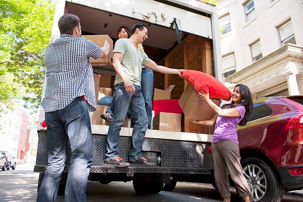Groupe de personnes qui rangent des cartons dans un camion de déménagement