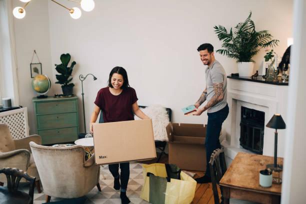 Un couple qui fait ses cartons de déménagement dans le salon de leur appartement