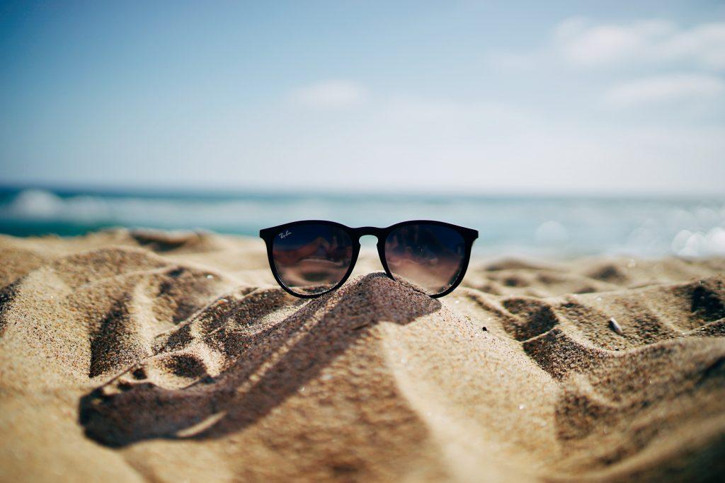 Plage avec lunettes de soleil posées sur le sable