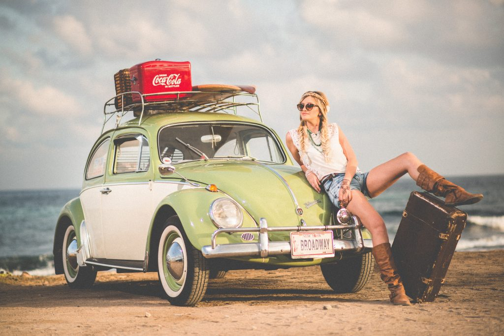 Jeune femme appuyée contre sa voiture verte chargée de bagages pour des vacances